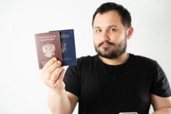 En man med ett skägg som rymmer ett pass av den Ryssland och Ukraina översättningen: - Ukraina Pass rysk federation royaltyfri foto