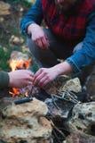 En man med ett skägg tänder en brand i skogen Arkivfoto