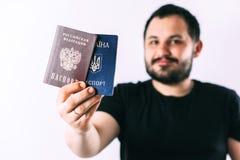 En man med ett sk?gg som rymmer ett pass av den Ryssland och Ukraina ?vers?ttningen: - Ukraina Pass rysk federation royaltyfri bild