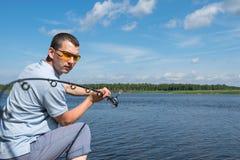 En man med exponeringsglas fiskar med en rotering på en flod royaltyfri bild