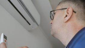 En man med exponeringsglas som rymmer en fjärrkontroll och på vänder luften som hemma betingar Delat system som fästas till arkivfilmer