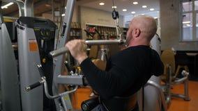 En man med en härlig kropp som baktill gör en övning på simulatorn, siktade muskler Sikt från den långsamma tillbaka 4Ken stock video