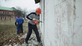 En man med en hålapparat som utanför bryter en vägg En man i en skyddande hjälm Rivningarbete arkivfilmer