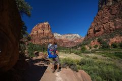 En man med hans behandla som ett barn pojken trekking i den Zion nationalparken, Utah, USA royaltyfri fotografi