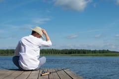 En man med en hatt sitter på en pir och önskar att fånga en fisk genom att använda rotering royaltyfria bilder