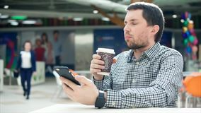 En man med koncentrerade sms för en blickmaskinskrivning på en mobiltelefon, i hans handkaffe