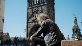 En man med långt lockigt hår men en skallig fläck som sitter på en bakgrund av brotornet av Charles Bridge lager videofilmer