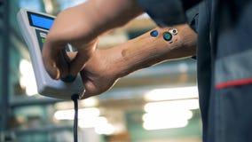 En man med modern protes vänder upp ett handtag på en fjärrkontroll, slut stock video
