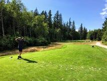En man med en mycket trevlig golfgunga som spelar en medeltal 3 Han är i hans följer igenom arkivfoton