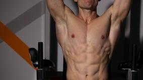 En man med en naken torso sitta-UPS med benet lyfter på horisontalstången i idrottshallen stock video