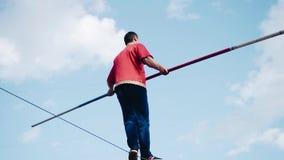 En man med en pol är på en kabel ovanför jordningen arkivfilmer