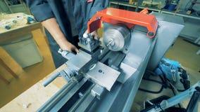 En man med prosthetic händer arbetar med en metalldrejbänk i en fabriksutrustning arkivfilmer