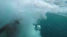 En man med en rinnande start dyker in i havet från klippan långsam rörelse stock video
