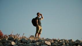 En man med en ryggsäck som ser in i avståndet och, är på berget Sund aktiv livsstil stock video