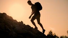 En man med en ryggsäck stiger till överkanten av berget på solnedgången Kontur av personen på solnedgången Sund aktiv arkivfilmer