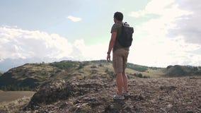 En man med en ryggsäckturist beundrar sikten av bergen ung handelsresande i bergen arkivfilmer