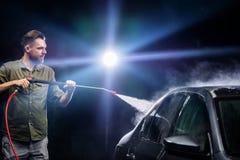 En man med en skägg- eller bilpackning tvättar en grå bil med en högtrycks- apparatur på natten i en biltvätt arkivbilder