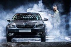 En man med en skägg- eller bilpackning tvättar en grå bil med en högtrycks- packning på natten i en shoppawash royaltyfria bilder