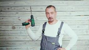 En man med en skruvmejsel Arbetarrepairman, byggmästare av den funktionsdugliga dräkten stock video