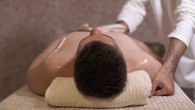 En man med en special svamp tvättar kroppen av en liggande man stock video