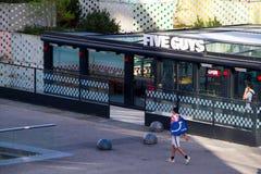 En man med en sportpåse promenerar grabbar för ett sportkafé fem i områdesLaförsvar i Paris arkivbild