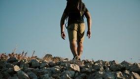 En man med en stor ryggsäck klättrar ett berg Praktiserande sund aktiv livsstil för ung man stock video