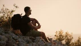 En man med en stor ryggsäck sitter på berget på solnedgången arkivfilmer