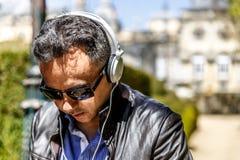 En man med svarta exponeringsglas lyssnar till musik med stor vit hörlurar, medan gå i, parkerar royaltyfri fotografi