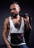 En man med tatueringar på hans armar Kontur av den muskulösa kroppen caucasian brutal hipstergrabb med modern frisyr som ser arkivbild