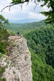 En man med en telefon står på en klippa med en brant stenig lutning och dalen med en tjock grön skog under royaltyfria foton