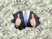 En man med tummar upp inom ramen för US dollarräkningar den 100 dollar nominalen fakturerar båda sidor Arkivfoton