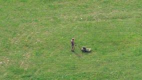 En man mejar gräset med en gräsklippare på en stor äng lager videofilmer
