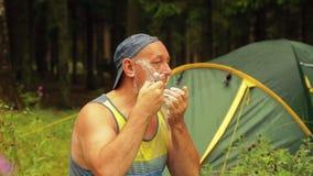 En man nära det turist- tältet rakar hans framsida stock video
