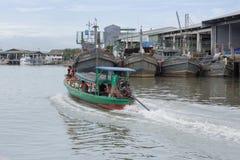 En man navigerar hans fartyg av passagerare går till den Kawthaung församlingen Arkivbild