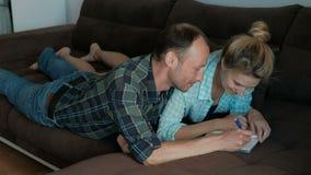 En man och en kvinna gör gemensamma anmärkningar i en anteckningsbok som ligger på soffan lager videofilmer