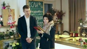 En man och en kvinna har en konversation på blomsterhandeln stock video