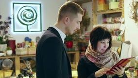 En man och en kvinna har en konversation på blomsterhandeln lager videofilmer