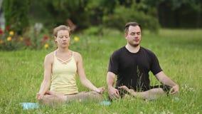 En man och en kvinna mediterar i salighet Unga yogainstruktörer övar i en stad parkerar på grönt gräs lyckat barn arkivfilmer