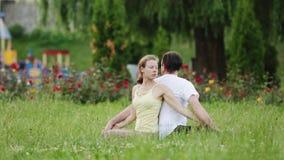 En man och en kvinna som sträcker, innan att göra övningar Unga yogainstruktörer övar i en stad parkerar på grönt gräs lager videofilmer