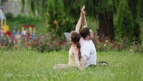 En man och en kvinna som sträcker, innan att göra övningar Unga yogainstruktörer övar i en stad parkerar på grönt gräs stock video