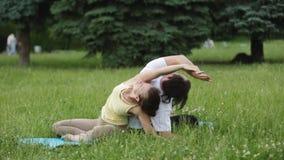 En man och en kvinna som sträcker, innan att göra övningar Unga yogainstruktörer övar i en stad parkerar på grönt gräs arkivfilmer
