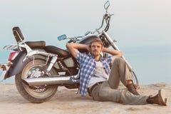 En man och en motorcykel. Arkivbild