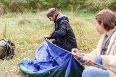 En man och en flicka satte ett tält i träna royaltyfria bilder
