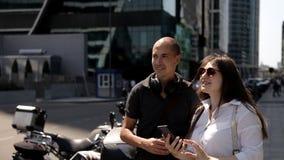 En man och en flicka som talar på gatan med skyskrapor arkivfilmer