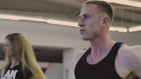 En man och en flicka utbildar på en trampkvarn i en konditionklubba stock video