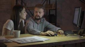 En man och en kvinna arbetar i kontoret på datoren och samtalen utmärkt, överansträngningar arkivfilmer