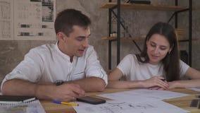 En man och en kvinna arbetar i laget som håller ögonen på teknisk uppgift i telefonen arkivfilmer