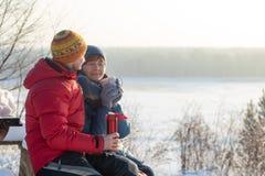 En man och en kvinna dricker te, kaffe, drinkar som utomhus sitter med en flodsikt Frostig solig vinterdag arkivfoto
