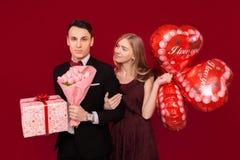 En man och en kvinna ger sig gåvor, hållgåvaaskar och ballonger, valentins begrepp, i studion på en röd bakgrund royaltyfri fotografi