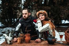 En man och en kvinna i historiska dräkter sitter på en tabell royaltyfri foto